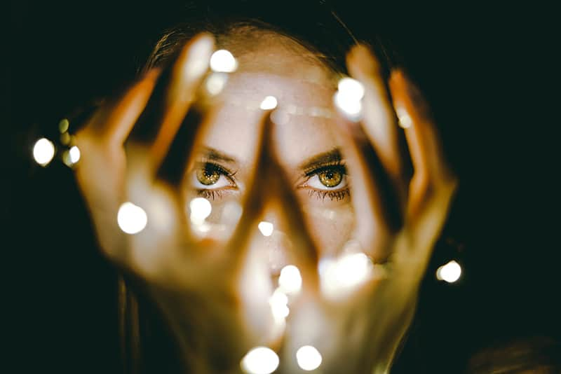 woman holding string lights in front of her eyes