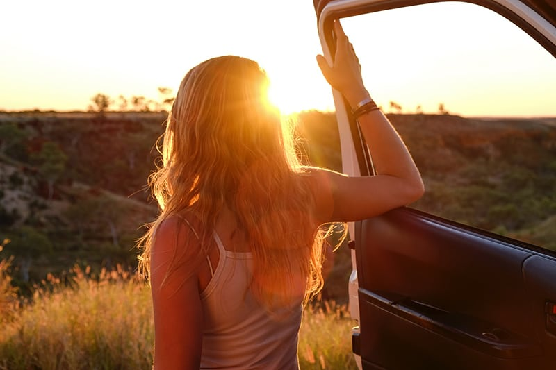 woman holding vehicle door and watching sunset