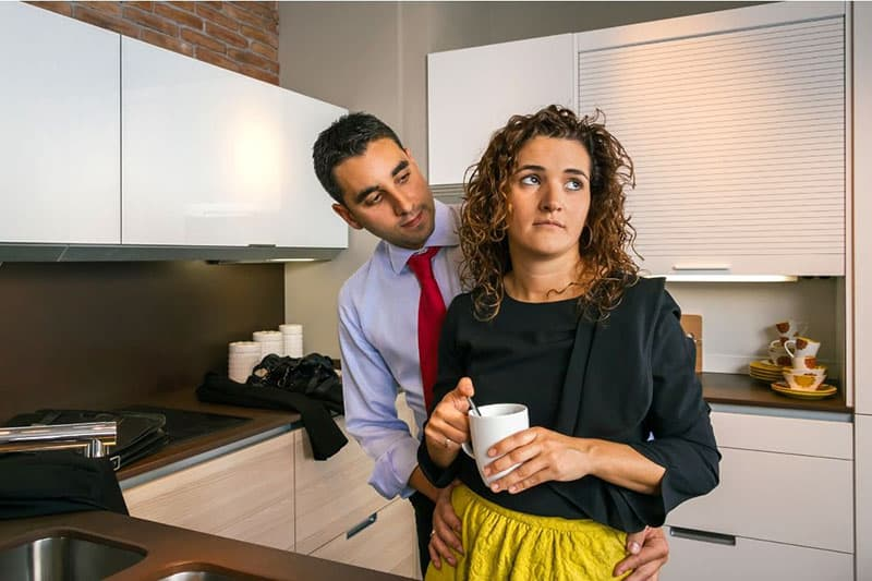 woman holding white cup and a man behind her holding her hips