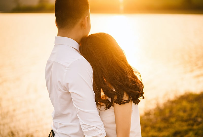 woman hugging man near the body of water