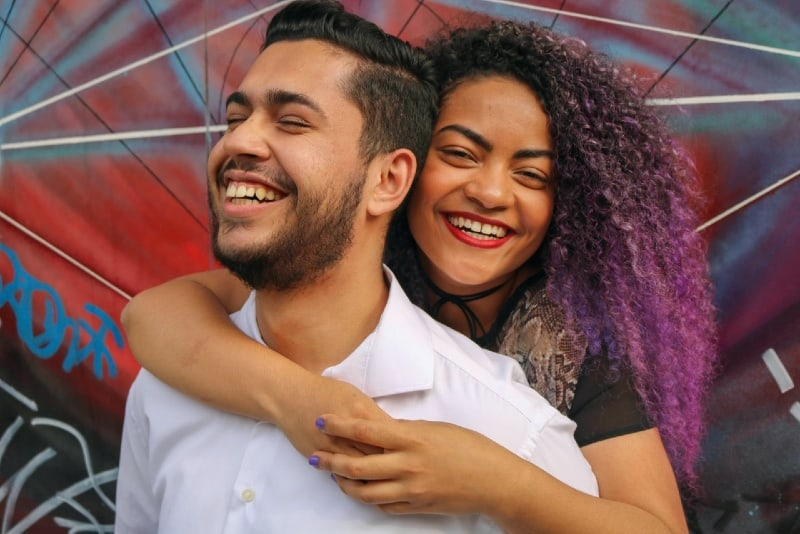 woman with curly hair hugging man from back