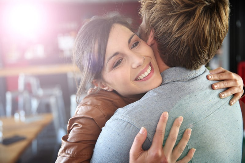 Smiling woman hugs her man