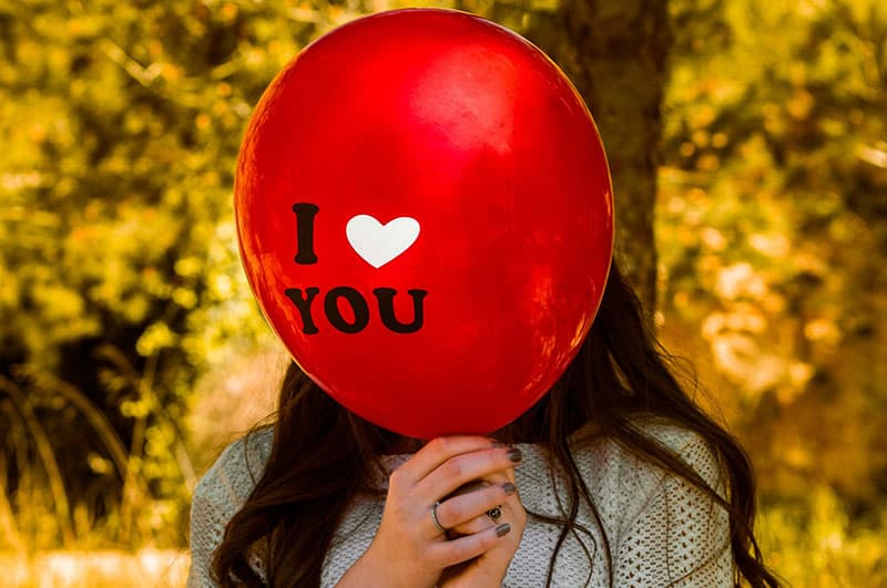 Woman covering face with I Love You Balloon