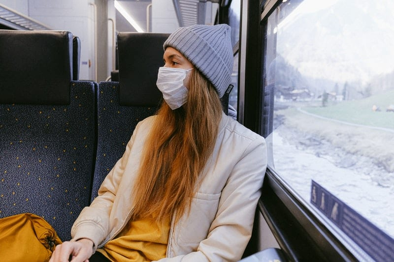 woman in a puv wearing mask and coat and a bonnet
