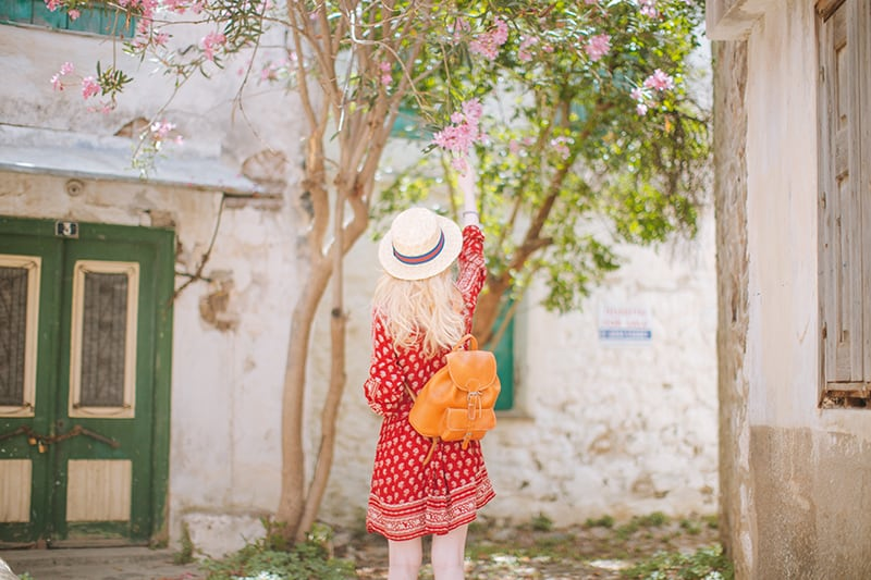 woman i a red dress with backpack reaching for a flower