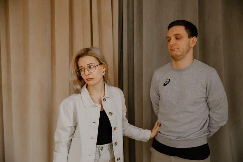 woman in beige blazer stopping a man in gray top