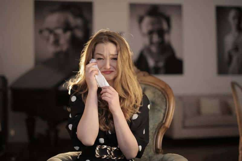 woman in black and white polka crying at home