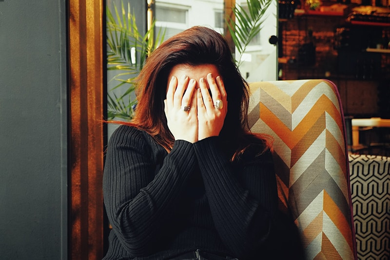 woman in black long sleeve shirt covering her face