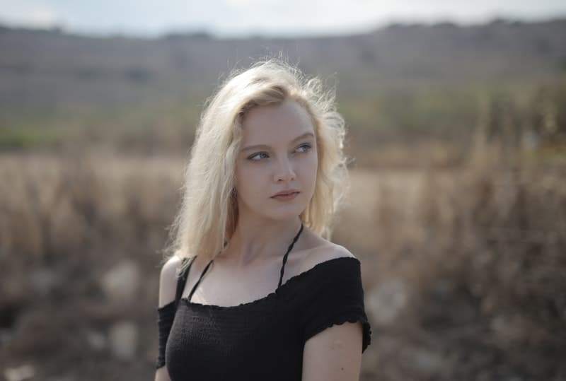 woman in black top with blonde hair near the field