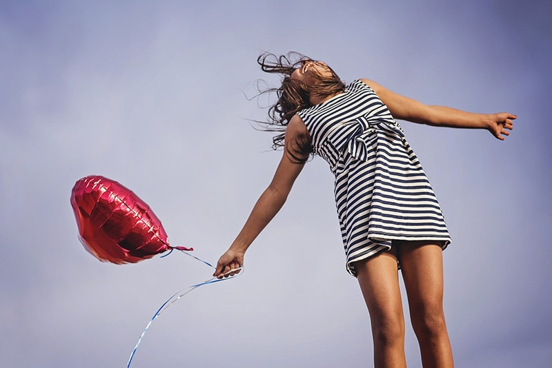 woman in black white dress holding red baloon
