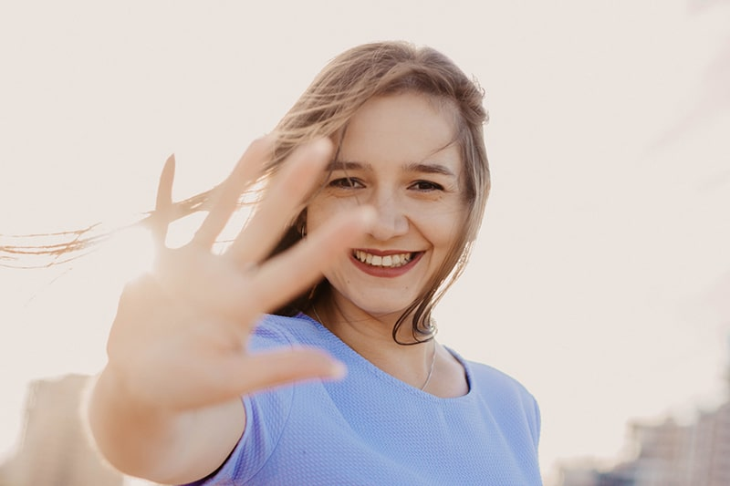 woman in blue top waving her right hand