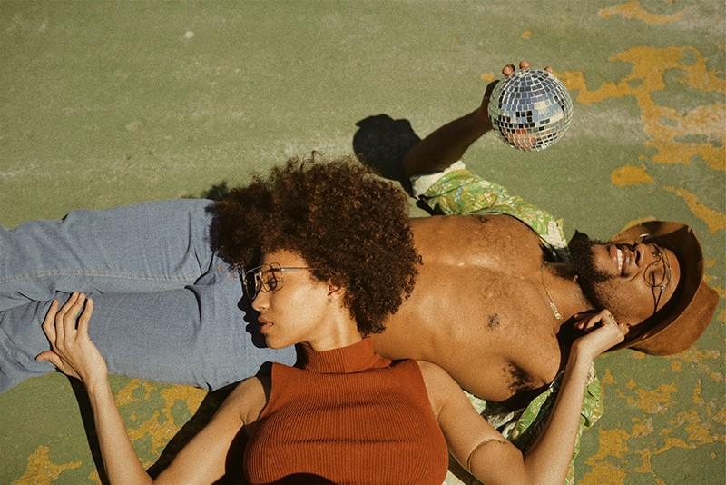 woman in top lying on man's stomach holding disco ball