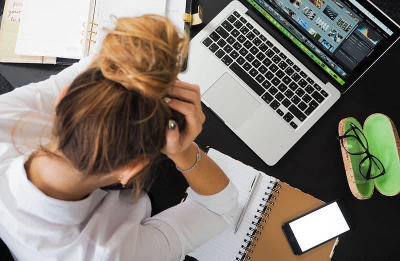 woman in desk displaying eyewear and lapto