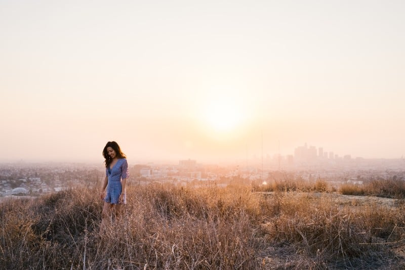 woman in blue dress standing in field during golden hour