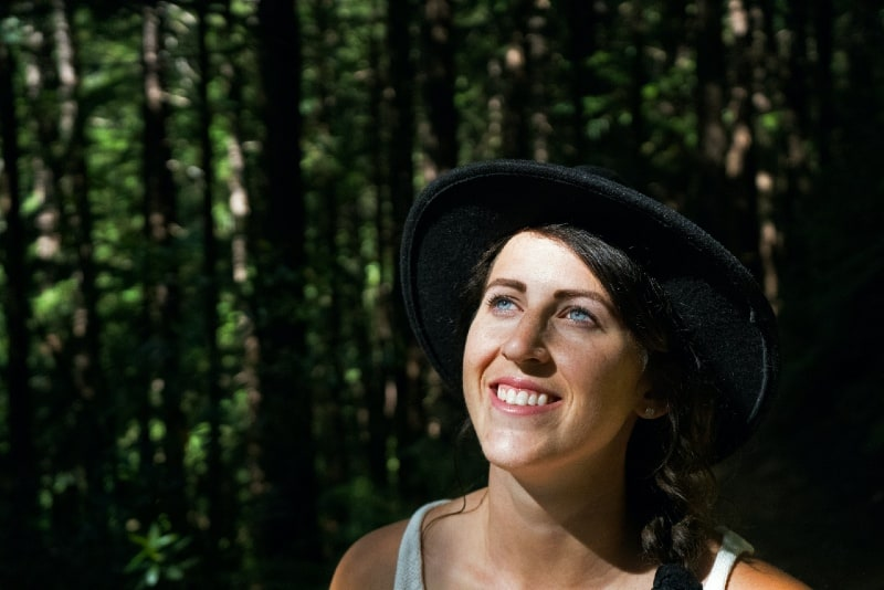 smiling woman with black hat standing in forest