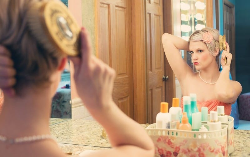 Beautiful woman using brush in front of a mirror