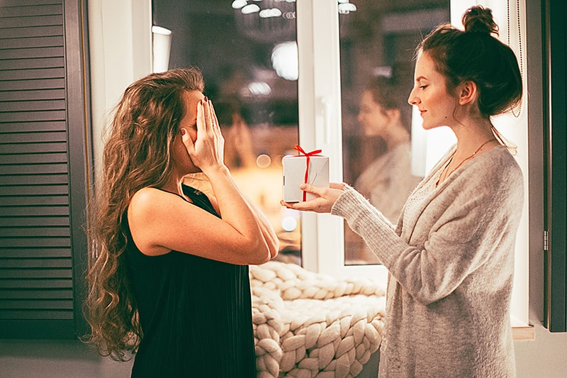 woman in gray cardigan giving white gift box to woman with covered eyes