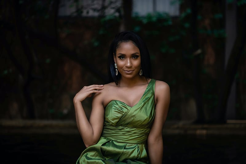 woman in green elegant dress touching shoulder with hand