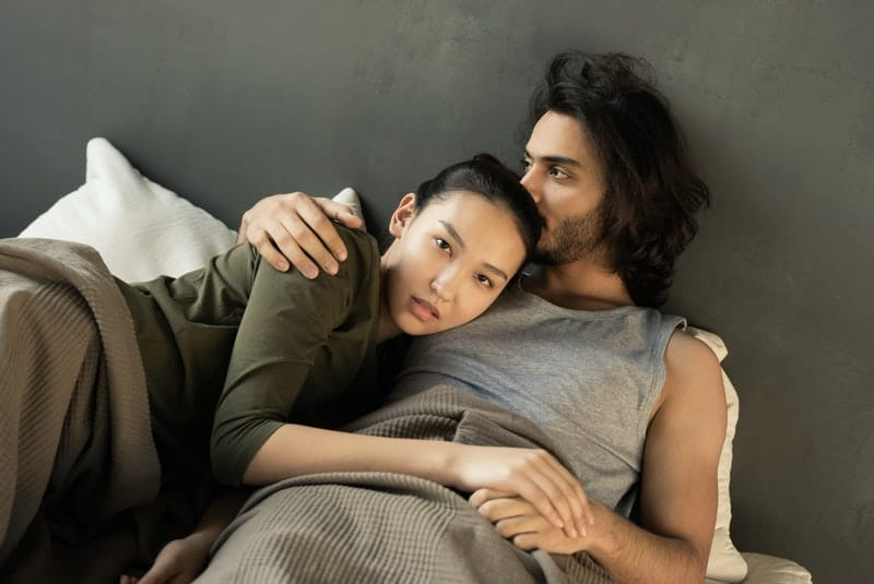 woman in green top lying on top of a man's chest on bed