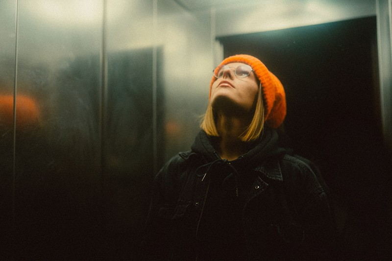 woman in orange knit cap looking up in the elevator