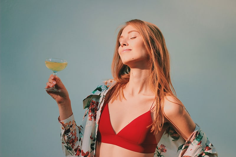 woman in red bikini top holding champagne glass