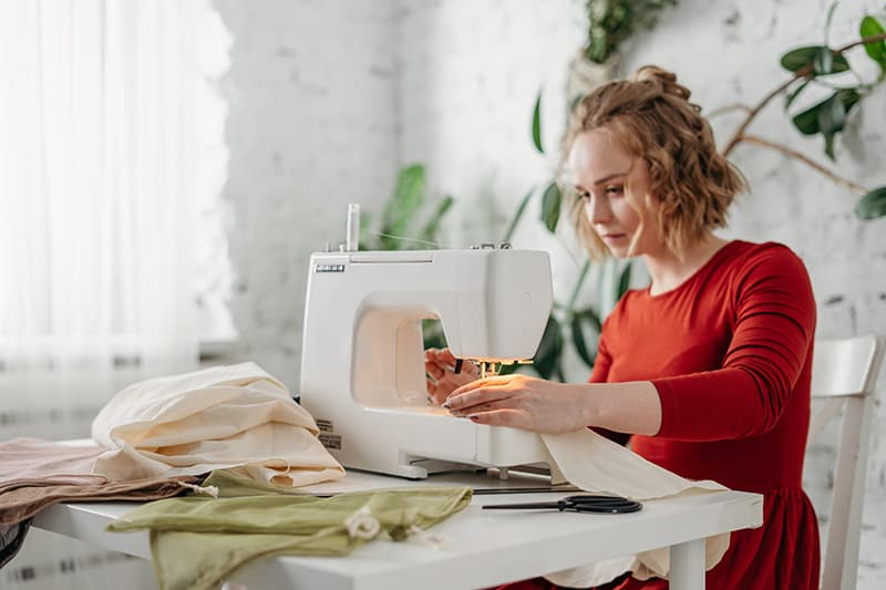 woman in red dress sewing while sitting on chair