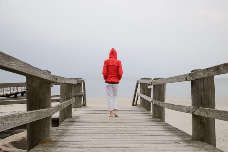 woman in red jacket walking across the bridge