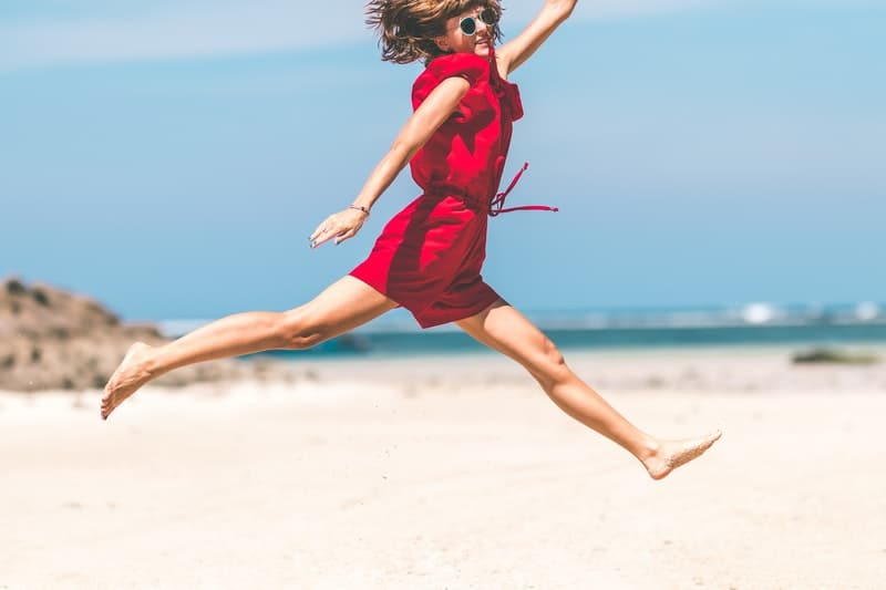 woman in red jumping in the seashore wearing sunglass