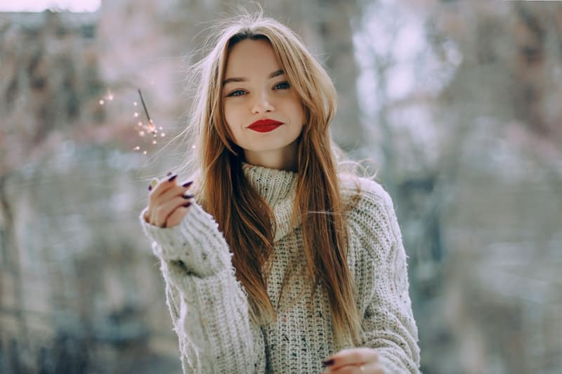 woman in red lipstick wearing gray sweater
