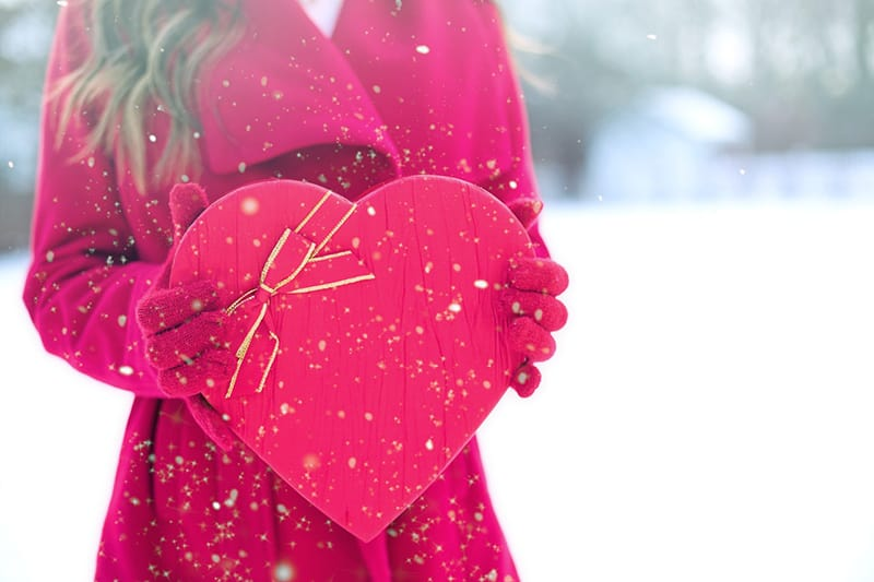 woman in red long sleeved coat holding heart shaped box