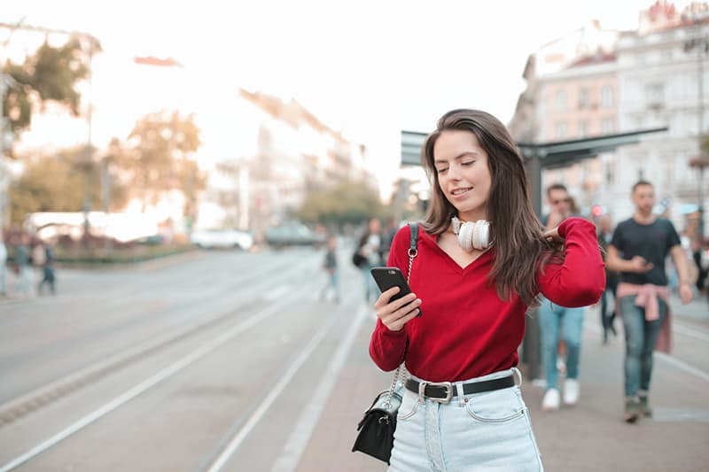 woman in red sweater using her phone while standing on sidewalk