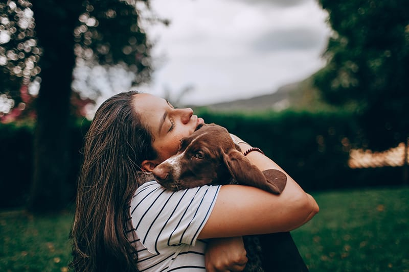 woman in white and black stripe shirt hugging brown dog