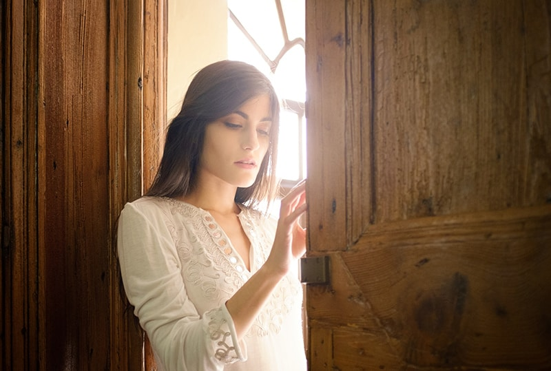 woman in white blouse leaning on brown wooden door frame