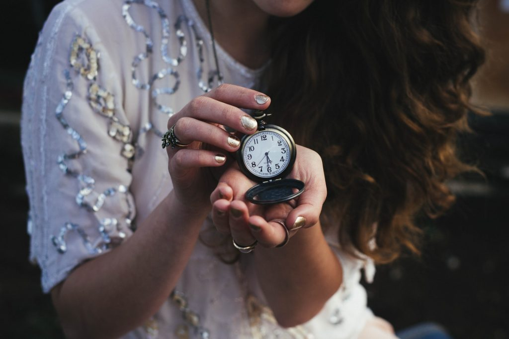 woman in white blouse holding black pocket watch
