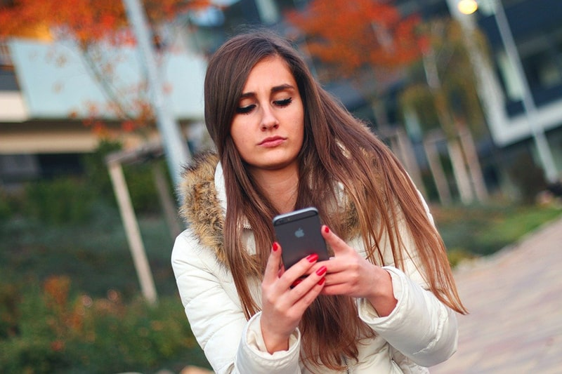 woman in white jacket using smartphone