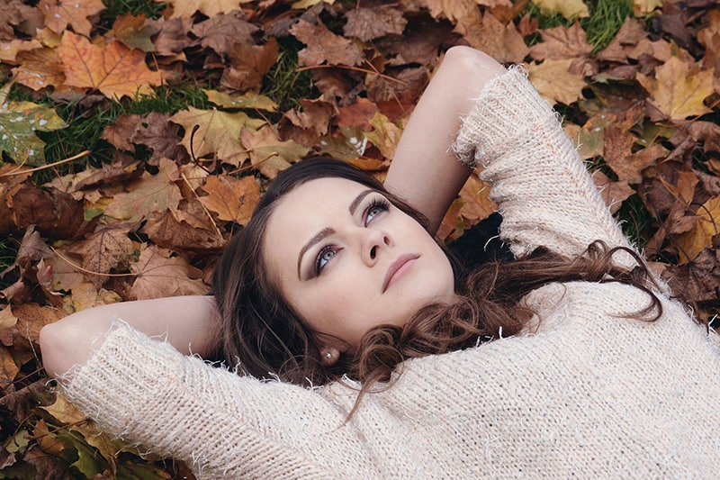 woman in white knit sweater lying on dried leaves