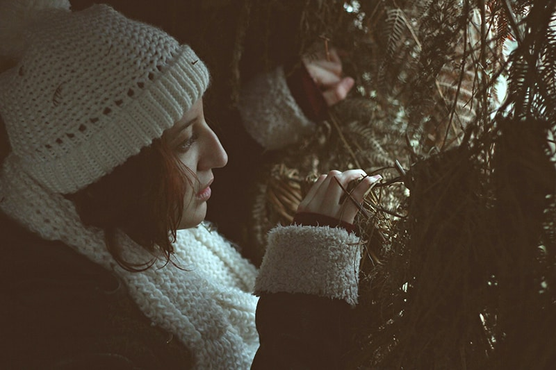 woman in white knitted cap peeking behind the tree