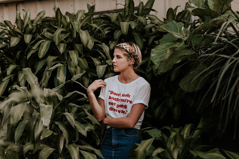 woman in white t-shirt standing near green plants looking aside