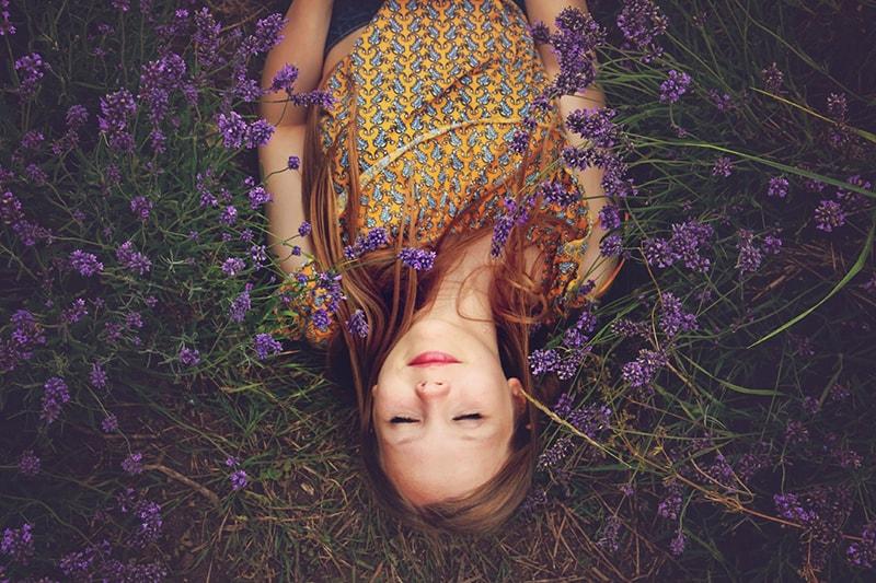 woman in yellow top sleeping beside lavenders