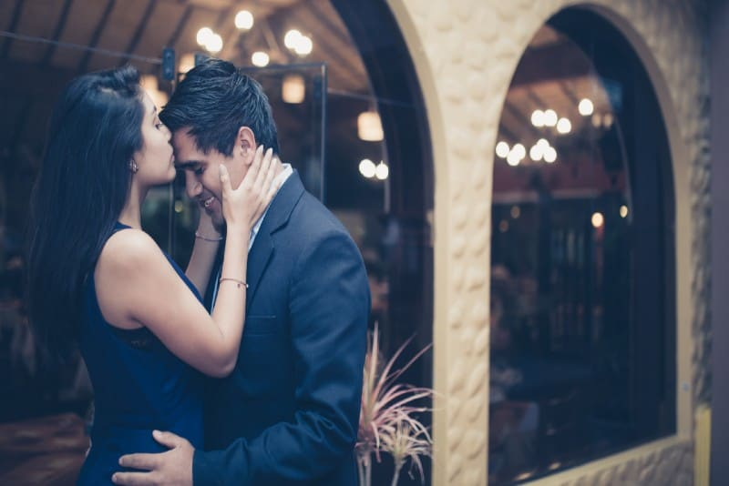 woman in black dress kissing man's forehead