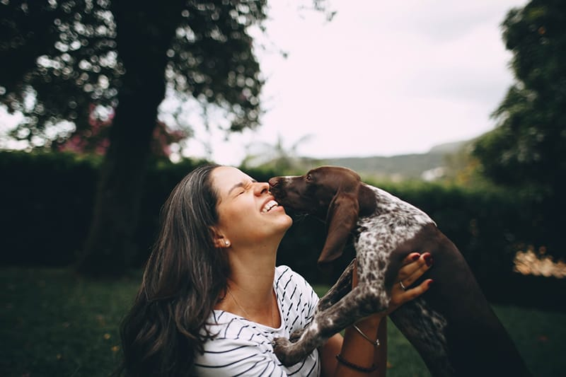 woman kissing the dog outdoors
