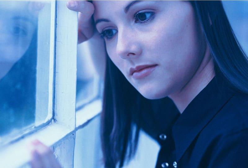 woman leaning head on glass window in blue photography scheme