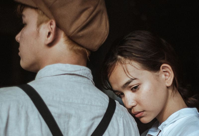 woman leaning her head to a guy in hat