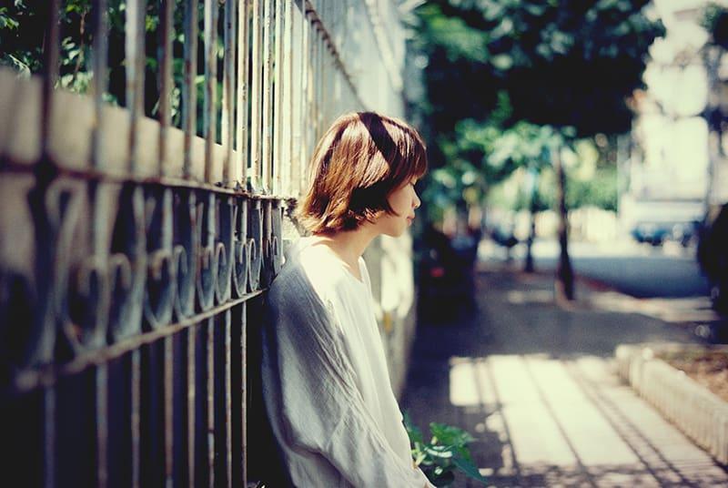 woman leaning on black steel fence near sidewalk