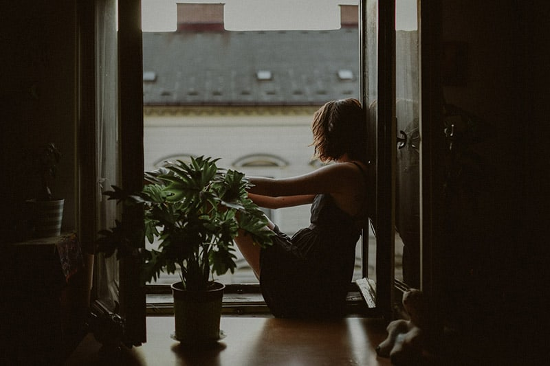 Woman on the floor leaning on balcony door staring outside