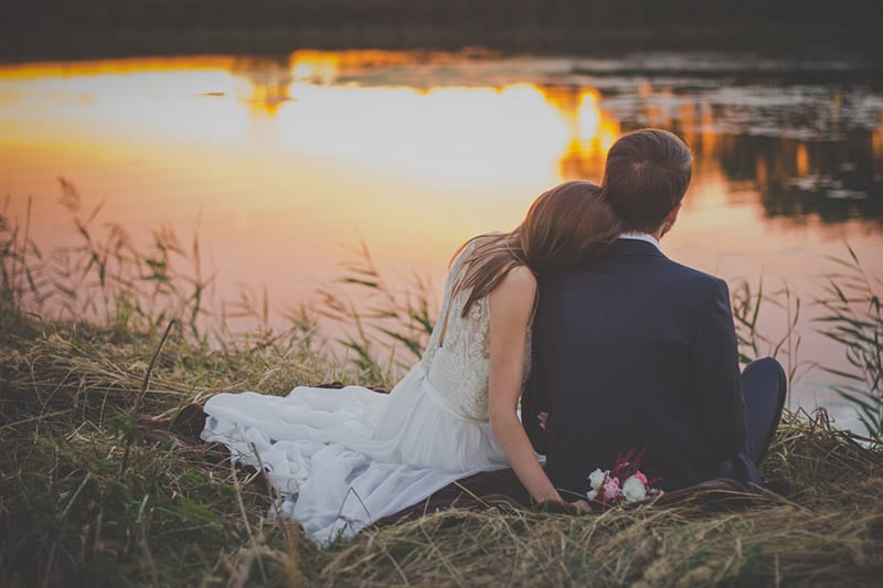 Woman in white dresss leaning on man's shoulders in front of lake
