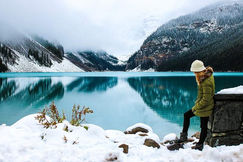 woman leaning on the wall near the lake in snowy time