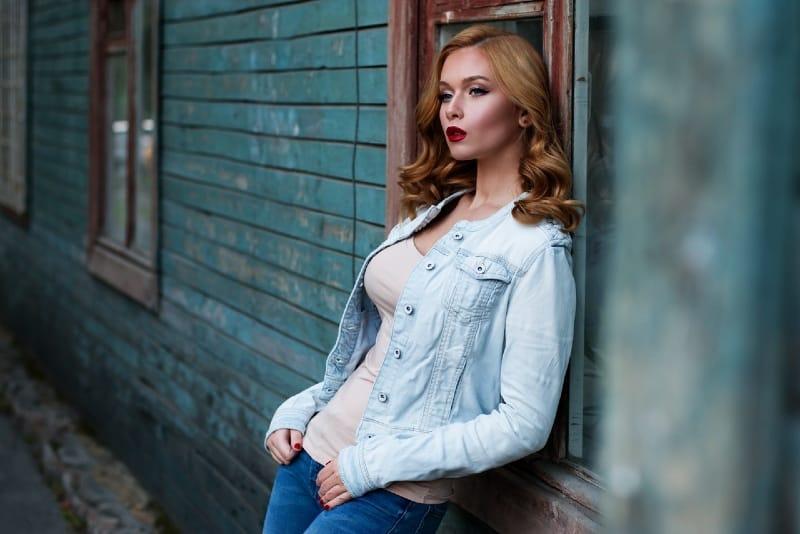 blonde woman in denim jacket leaning on window