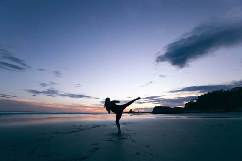 silhouette of woman kicking on mid air on beach