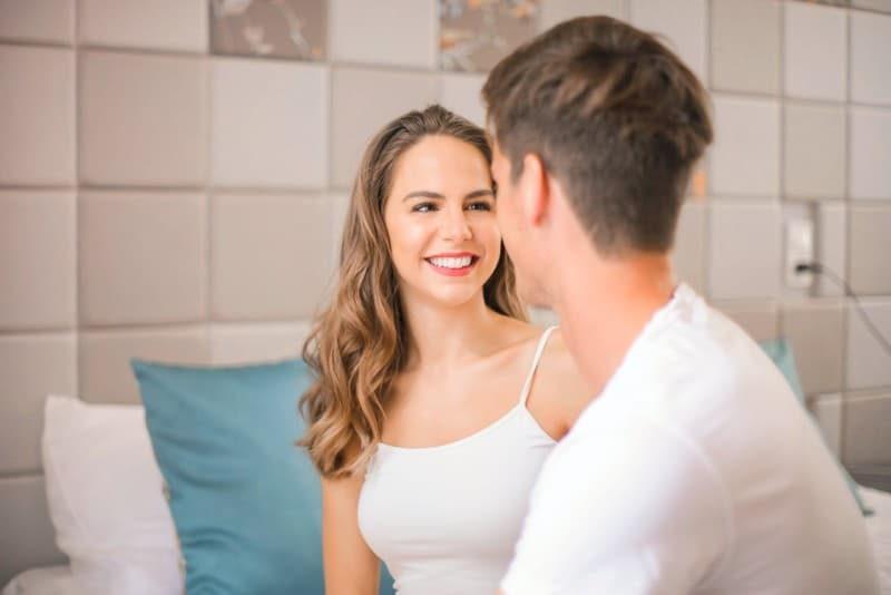happy woman in white top looking at man in bedroom